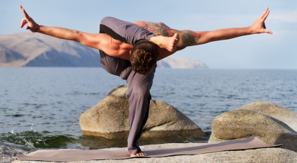 Man practicing yoga outside, challenging one-legged balancing pose