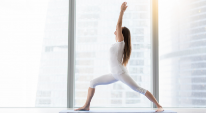 A yoga woman in Warrior 1 Pose (Virabhadrasana I) for strength and stability