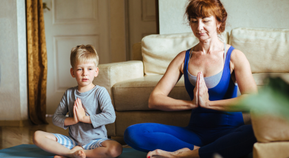 Child practicing yoga with an adult in Seated Pose