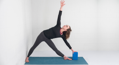 yoga woman practicing triangle pose trikonasana with block
