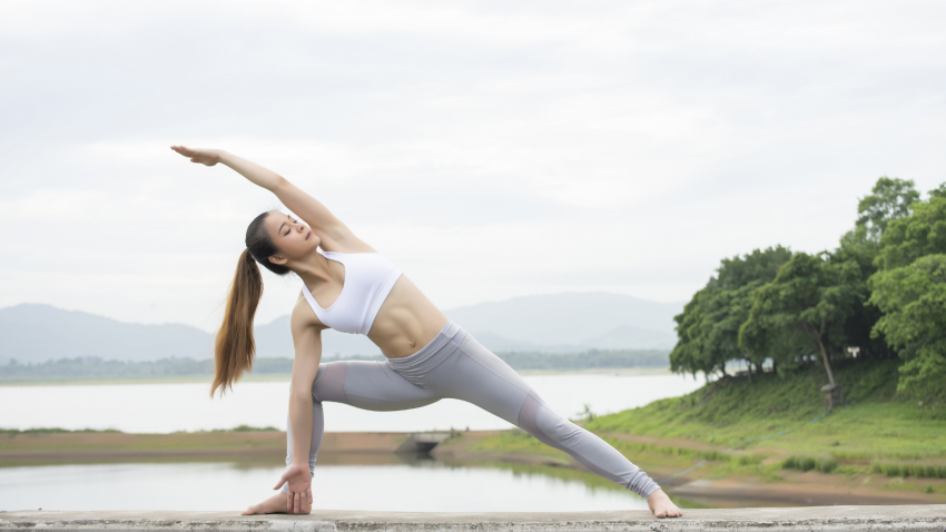 Woman practicing Yoga's Extended Side Angle Pose in the morning with strong energy lines