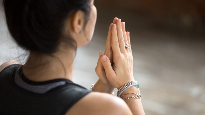 Namaste gesture close up photo, woman practice yoga representing the opening of the heart chakra
