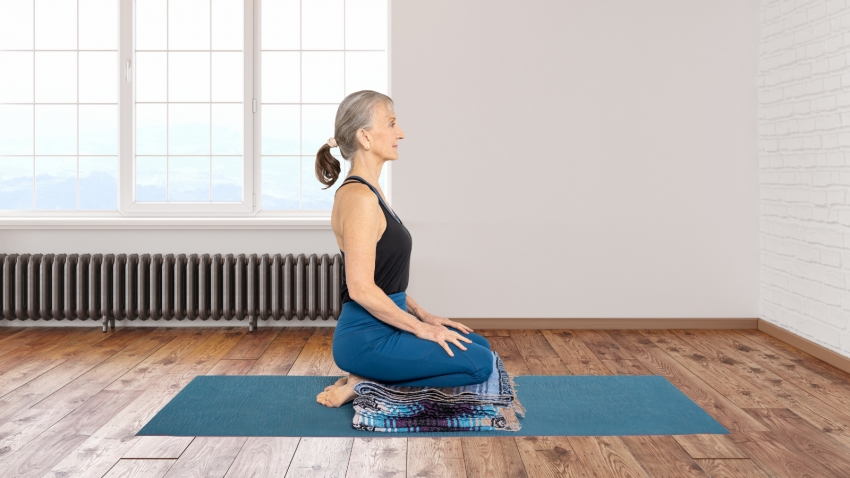 Yoga student enjoys the benefits of Hero Pose with a blanket to protect knees, hips, and ankles