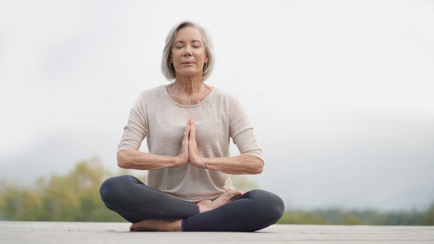 Older woman practicing meditation outdoors.
