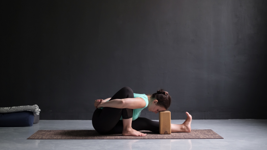 woman practicing bound janu sirsasana with block for support.