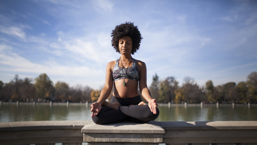 Woman practicing yoga in cross-legged seated pose to reduce stress