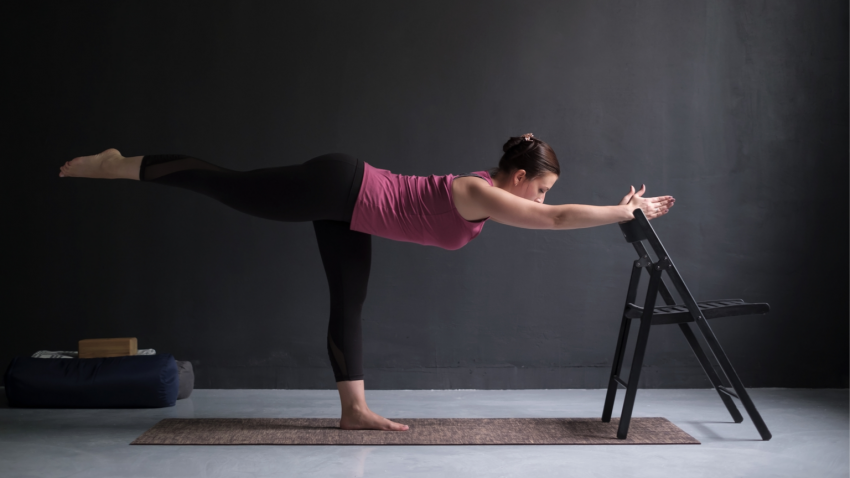 yoga woman practicing Warrior III pose with Chair modification