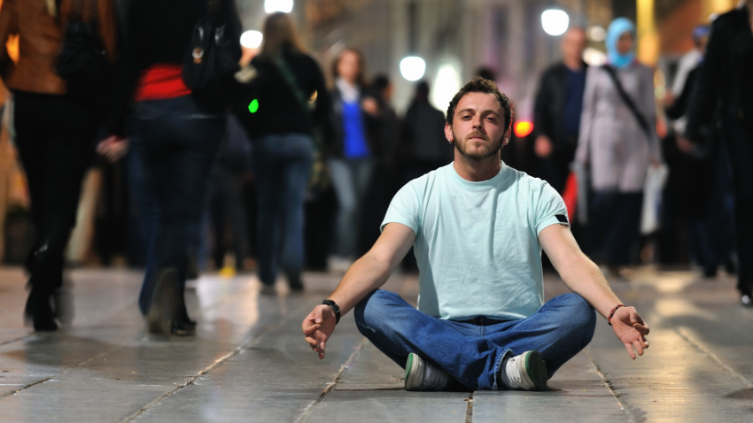 Man practicing meditation on the street
