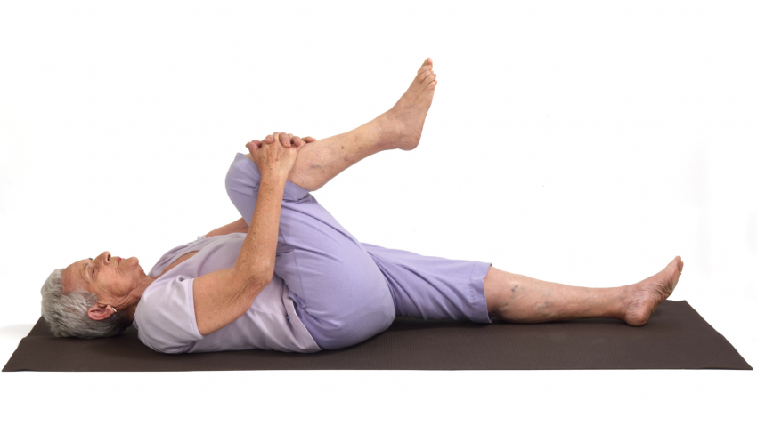 Older woman practicing yoga Apanasana