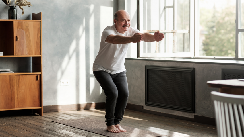 older man practicing yoga for strong thighs, chair pose