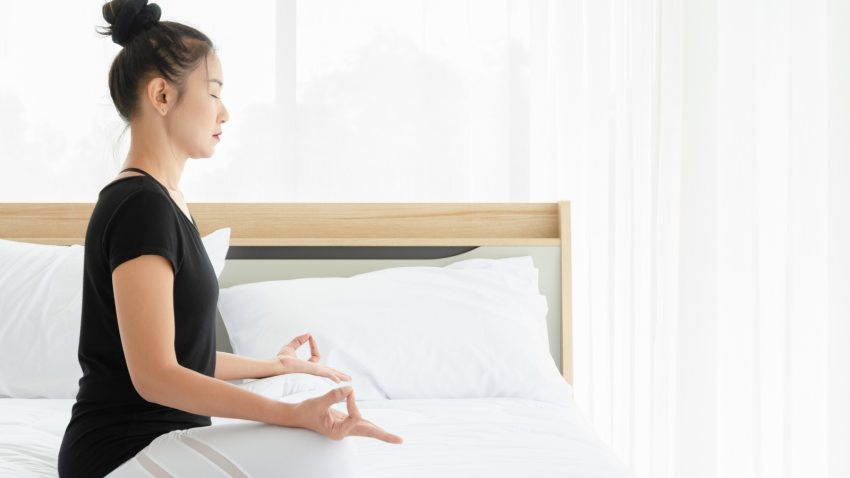 female yoga student practicing meditation for better sleep