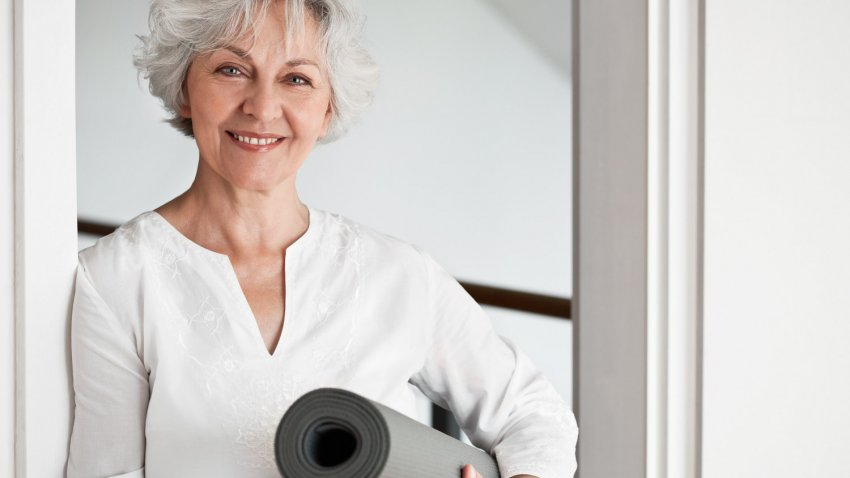 older woman with yoga mat