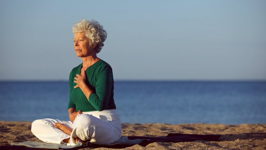 Woman practicing yoga meditation for cancer recovery benefits