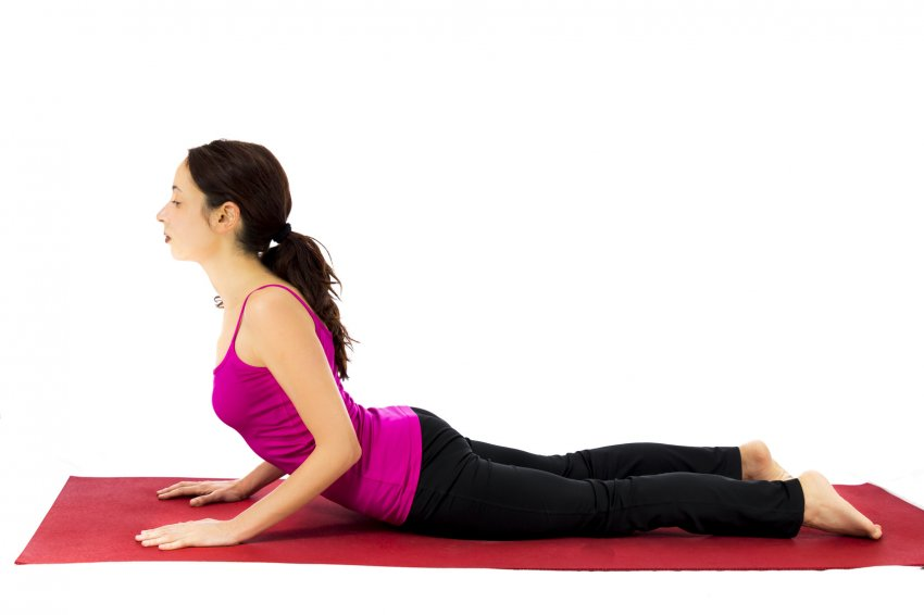 Woman in Cobra Pose (Bhujangasana) practicing beginning yoga
