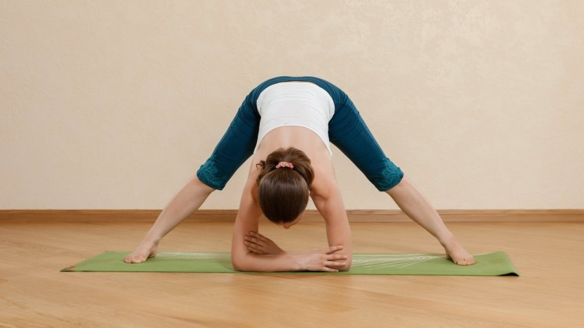 Woman doing Wide-Legged Standing Forward Bend (Prasarita Padottanasana)