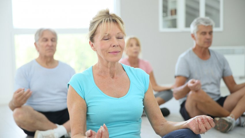 People in a yoga class in Lotus Pose (Padmasana) with eyes closed