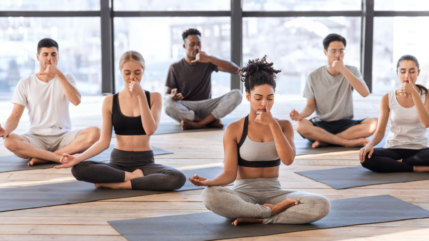 Yoga students practicing breathing exercises to improve their vital lung capacity