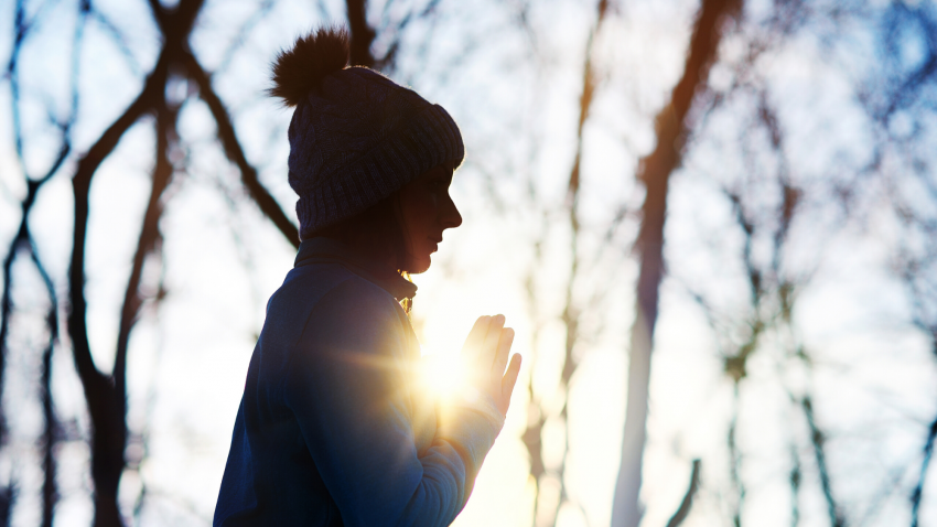 woman practicing meditation in winter forest