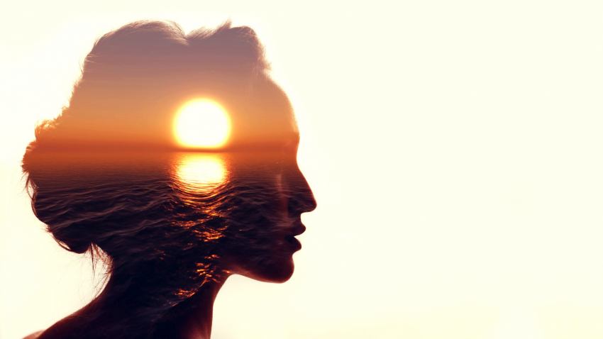 Woman reflecting on yoga practice at dawn with sunrise ocean superimposed on her face