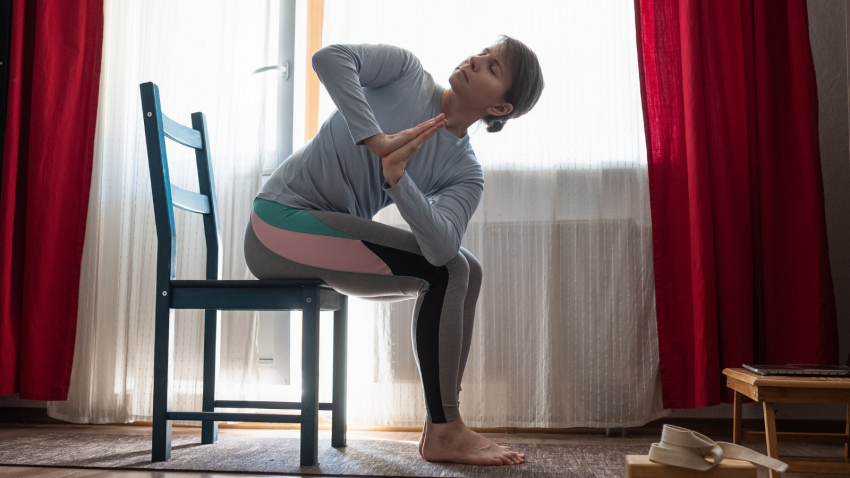 female yoga student practicing yoga with a chair at home.