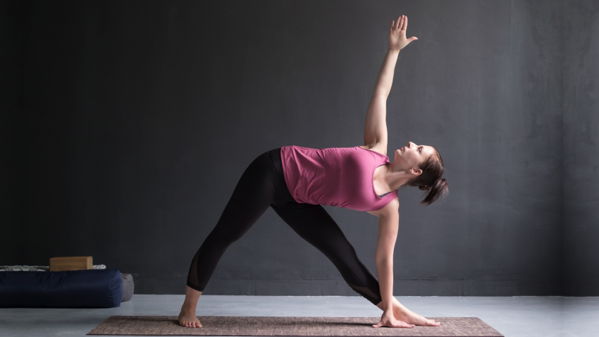 woman practicing yoga triangle pose