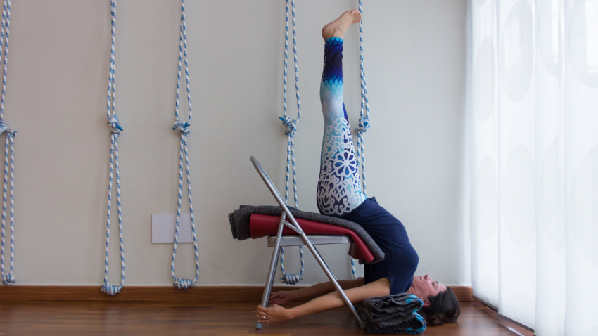 Female yogini preparing urdhva dhanurasana modification, upside down with legs straight up doing back bend exercise using chair, mats and blankets as props