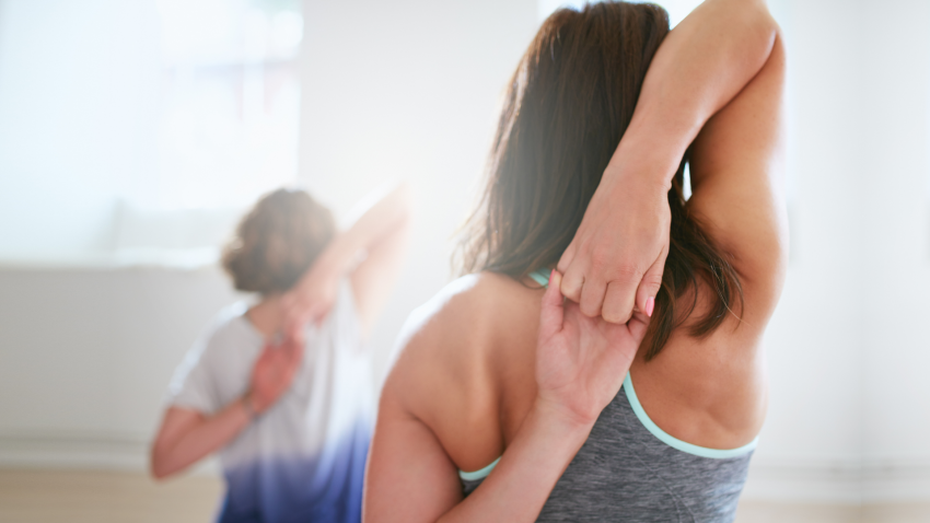 A woman practicing yoga and clasping her hands behind her back, muscle memory