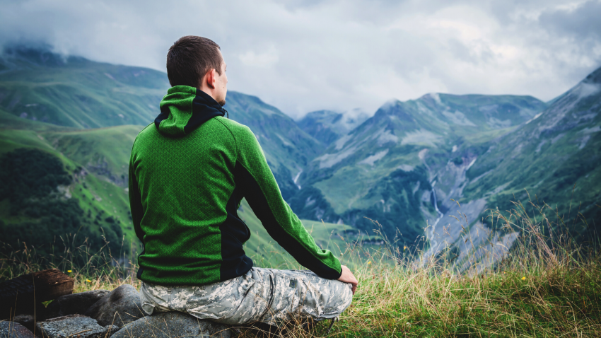 veteran yoga man meditating outside in mountains