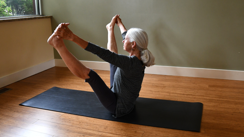 Woman practicing yoga upward facing wide leg forward bend, Urdhva Mukha Prasarita Padottanasana
