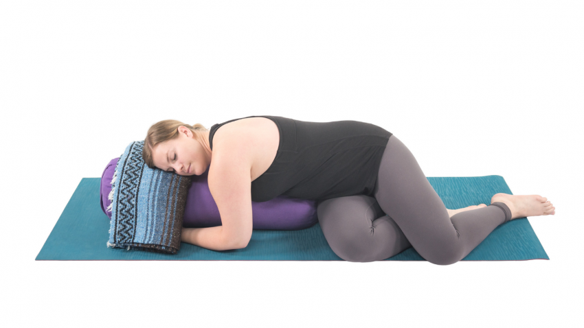 Woman practicing restorative yoga with props to decrease inflammation