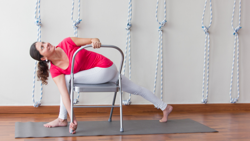 Middle aged woman practicing Iyengar Yoga Revolved Crescent Lunge with chair