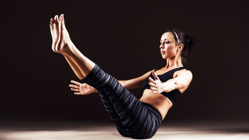 Woman in Boat Pose (Navasana), a yoga pose that encourages tapas or inner fire