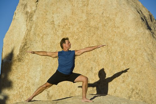 Man practicing yoga asanas, Warrior II pose (Virabhadrasana II), that can help lower high blood pressure naturally.