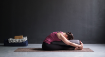 Female yoga student practicing seated forward bend (paschimottanasana) with yoga bolster for support.
