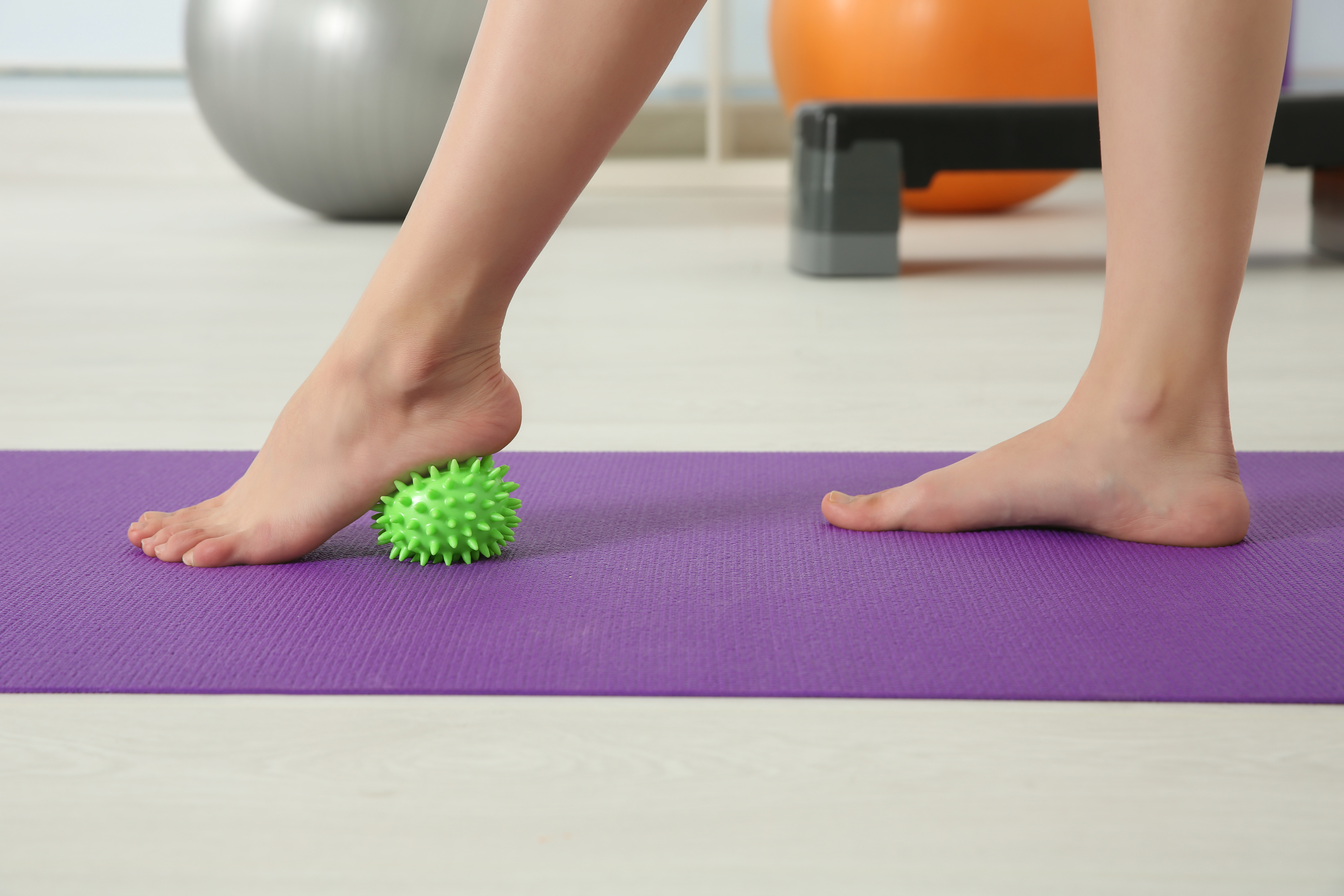 A woman massaging her foot using therapy balls, practicing yoga to strengthen and care for feet