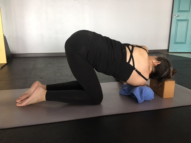 Woman practicing yoga, in thread-the-needle pose (Parsva Balasana), with props modification for neck and shoulder pain