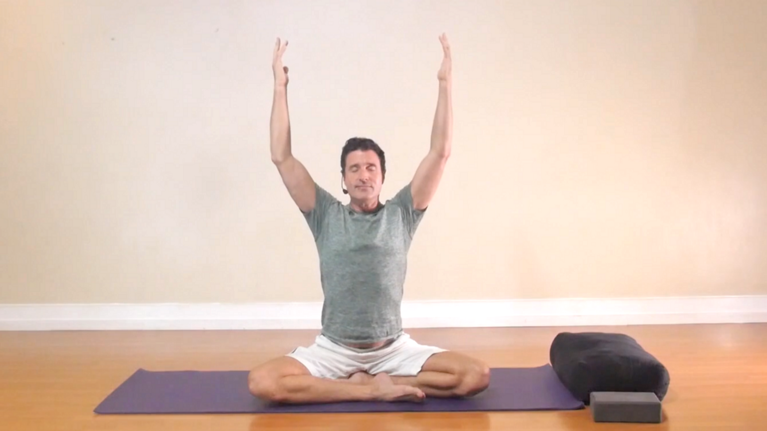 James Knight practicing Gentle Somatic Yoga seated pose arms raised