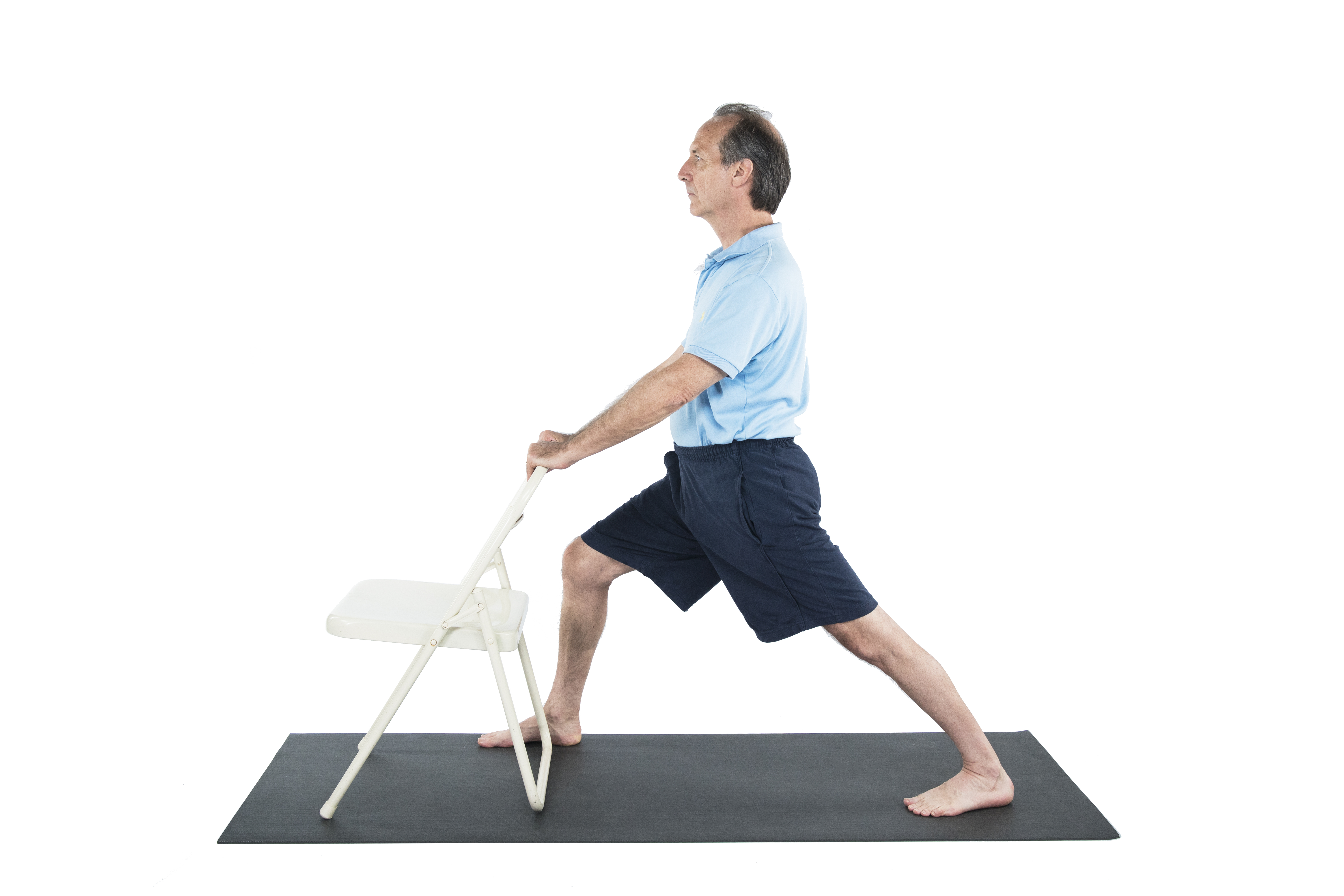 A man practicing Warrior 1 pose (Virabhadrasana I) with a chair to warm up the hips in preparation for Warrior 2 yoga pose